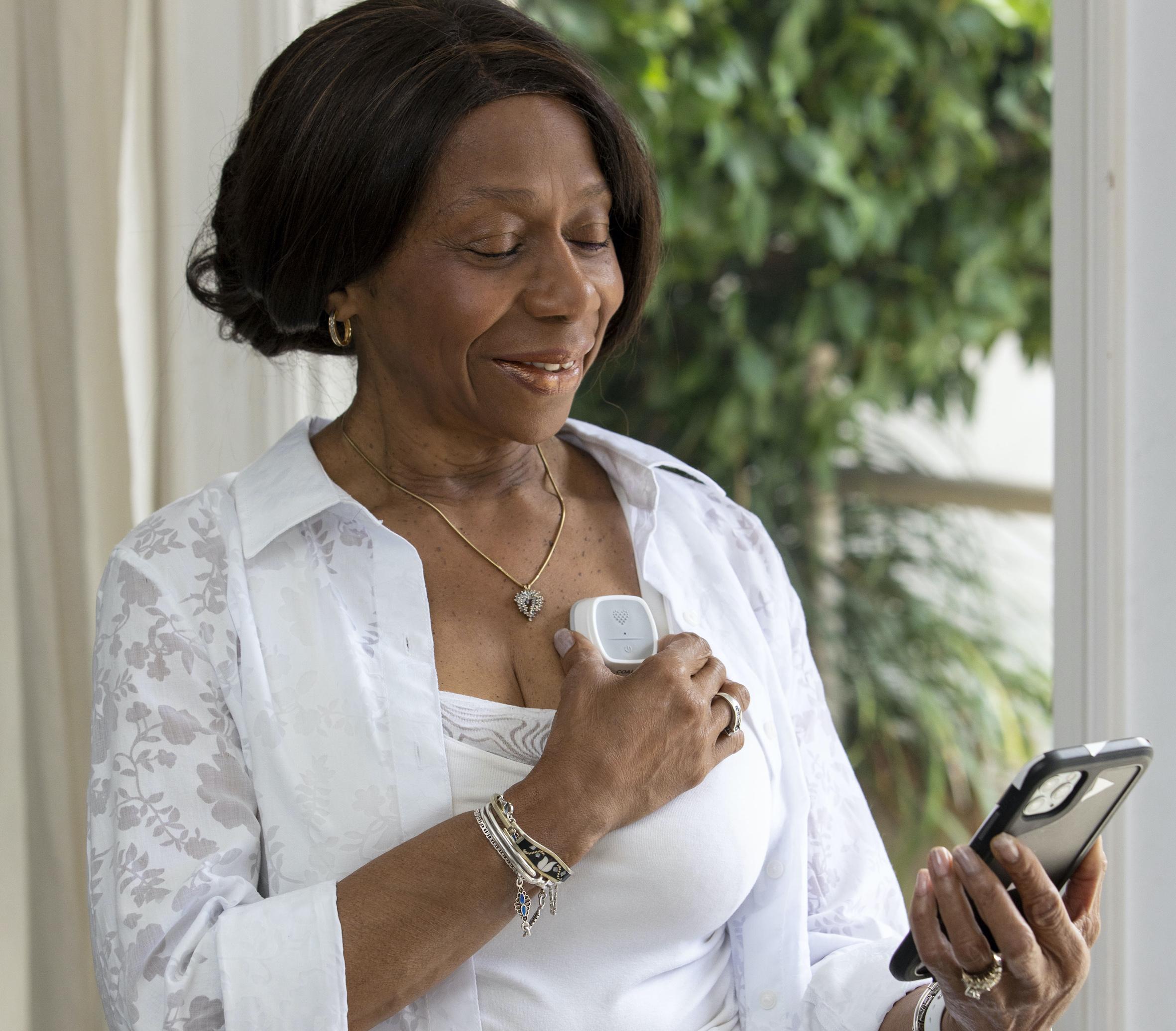 Woman using Coala Connect Rx service for measuring ECG