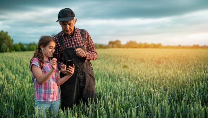 Senior farmer and his granddaughter using smart phone outdorrs in field.