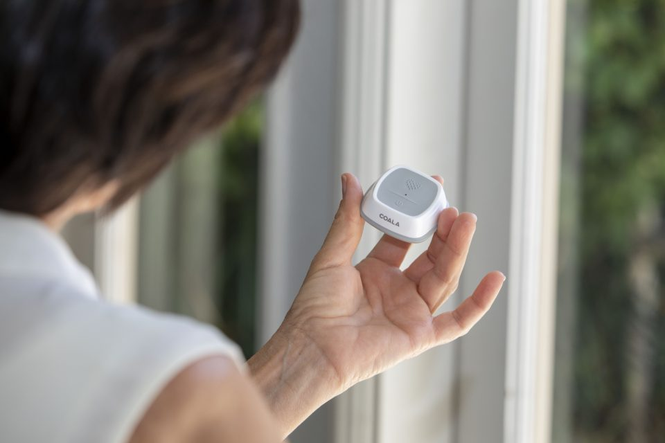 Woman holding grey and white Coala Heart Monitor with front up